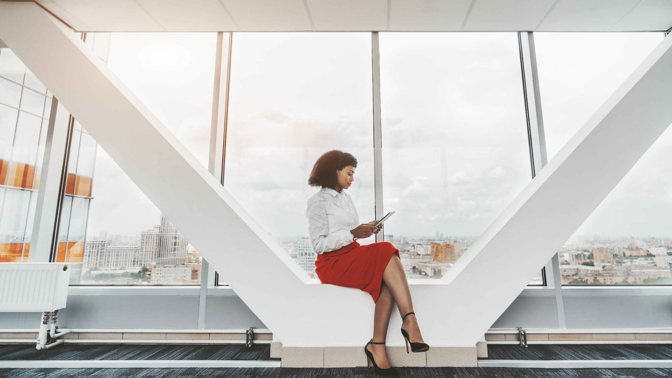 A young African-American businesswoman with a digital tablet indoors of a bright passageway in an office skyscraper; a charming biracial female with a tablet pc near the window in a business high-rise